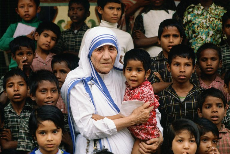 Mother Teresa accompanied by children at her mission in Calcutta