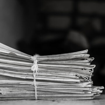 Black and white pack of newspapers on a table Image Credit: deccanherald.com